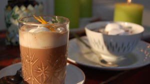 Ett glas med varm choklad toppat med vispgrädde och rivet apelsinskal.