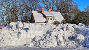Stor snöhög framför ett hus