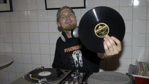 Rapartisten Paleface visar upp en LP, sitter bakom ett DJ-bord.