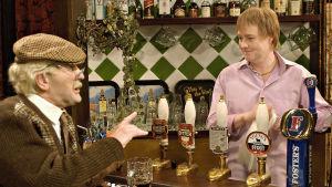 Norman (Frank Boyle) ja pubin isäntä Jules (Eamonn Riley) jutustelevat tiskin ääressä.