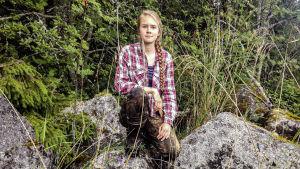 Kvinna i vildmarkskläder sitter på mossbeklädda stenar i skog.