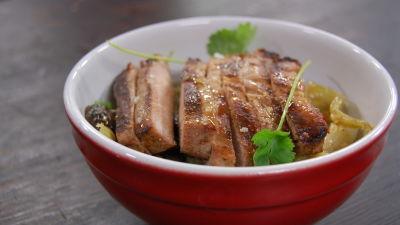 En röd skål med en portion nudelsallad. Högst upp på portionen ligger en bit uppskuret kött toppad med gröna örter.