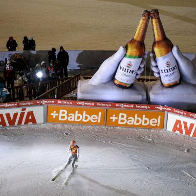 Severin Freund bromsar in framför två stora ölreklamflaskor.