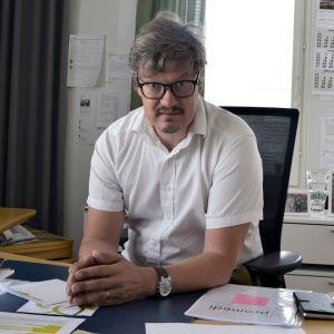 En man med glasögon och vit kortärmad skjorta sitter bakom ett skrivbord.