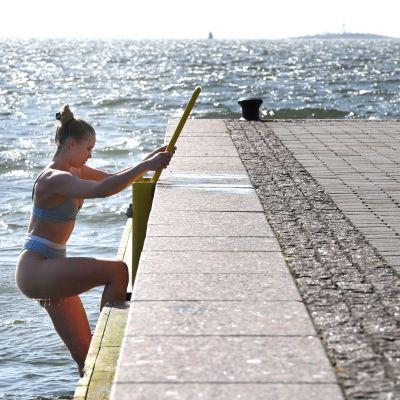 En simmare vid Eirsastranden i helsingfors en varm vårdag, den 11 april 2021.