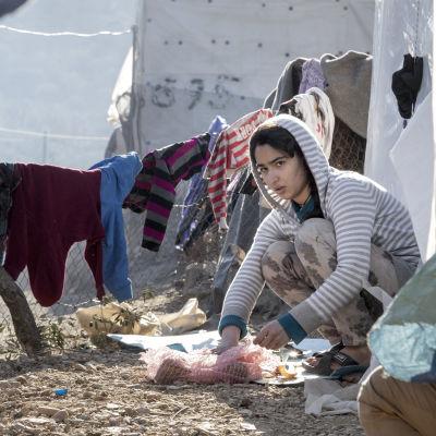 Pakolaistyttö pilkkoo ruokaa maassa Morian pakolaisleirillä.