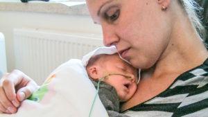 Äiti pitää sylissään pientä vauvaa, jolta lähtee nenästä letku. Ovat selvästi sairaalassa.