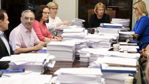 Grundlagsutskottet är samlat bakom högar av papper.