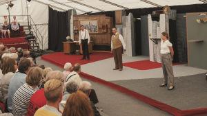 Tre skådespelare på en scen, publik på läktare.