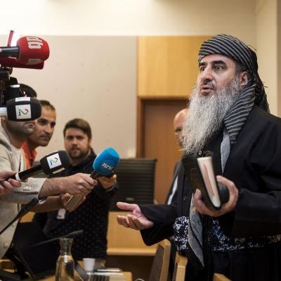 Mullah Krekar seisoo toimittajien mikrofonien edessä oikeussalissa