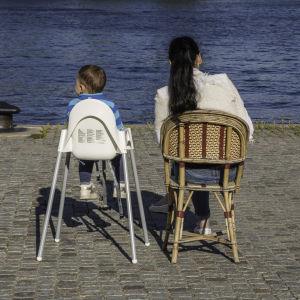 Mamma och barn sitter på var sin stol vid vattnet.