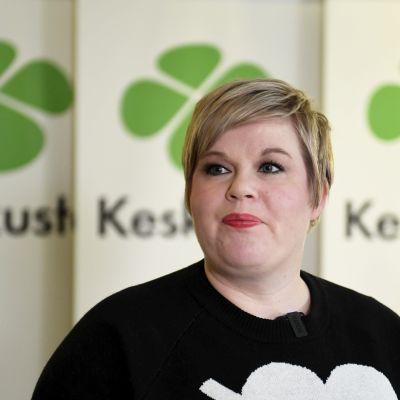 Annika Saarikko, taustalla keskustan banderolleja.