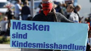 """En tysk man bär en skylt där det står """"munskydd är barnmisshandel"""" under en demonstration mot coronarestriktioner i början av oktober 2020"""