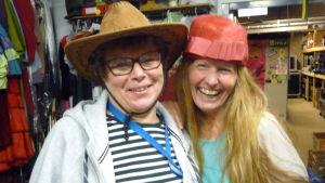 Maggi Ahlfors med stetsonhatt, Tiina Grönroos med röd pillerburk/hatt på huvudet, båda skrattar.