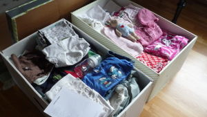 två papplådor fyllda till brädden med babykläder.