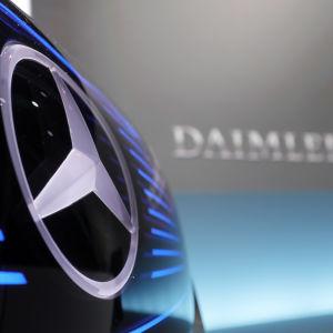 Biltillverkaren Daimlers logo i förgrunden, texten Daimler syns suddigt i bakgrunden.