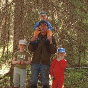 Markku Kuha kolmen lapsensa kanssa kesäisessä kuusimetsässä. Tytöt seisovat isänsä molemmilla puolilla. Poika istuu isänsä harteilla.