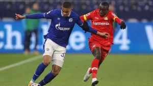 Två fotbollsspelare i närkamp. Mannen till vänster i blå skjorta, vita shorts och blå strumpor har bollen. Mannen i helröd dräkt närmar sig honom till höger.