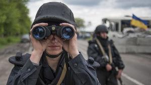 Ukrainsk soldat tittar i en kikare nära Slovjansk.