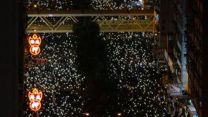 Människor håller uppe sina telefoner som ljus i en demonstration i Wan Chai i Hongkong söndagen den 8 december.