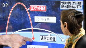 En fotgängare i Tokyo tittar på en tv-sändning om det senaste nordkoreanska missiltestet på tisdagen 4.7.2017.