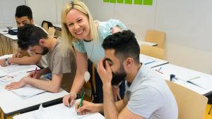 Opettaja näyttää oppilaalle miten tehtävä tehdään ja molemmat nauravat