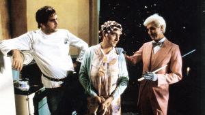 Scen ur Monty Python The Meaning of Life. Terry Jones i mitten med papiljotter i håret. John Cleese till vänster och Eric Idle till höger.