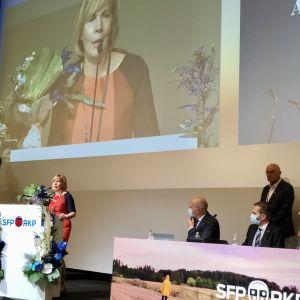 Anna-Maja Herniksson i talarstol och på storskärm med blombukett vid partidagen.