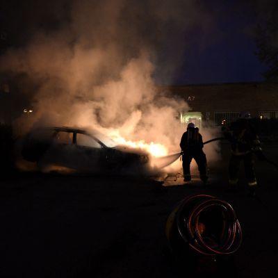 En brandman släcker brinnande bil i Kista efter kravaller 22.05.2013