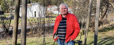 En äldre man står iklädd röd jacka framför en gunga på en bakgård.