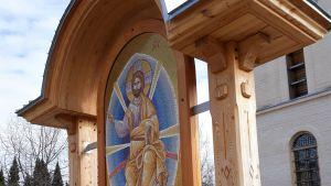 Mosaiikki-ikoni seisoo Puuartin tekemän puisen holvikaarikatoksen suojissa ortodoksisen seminaarin edessä.