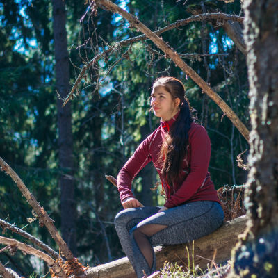 En kvinna iklädd sportkläder sitter på en sten ute i skogen. Hon ser nöjd ut. Solen lyser på hennes ansikte.