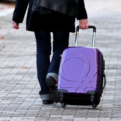 Kvinna drar en kappsäck efter sig