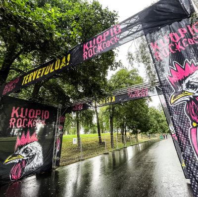Kuopiorock-festivaalin tyhjä sisäänkäyntiportti odottaa sadesäällä festarivieraita.