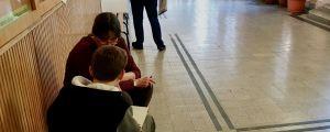 En lärare hjälper en pojke med läxan på en bänk i korridoren i en skola i Budapest.
