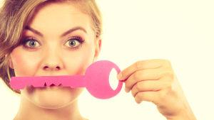 Kvinna ser in i kameran, håller upp stor rosa leksaksnyckel framför munnen