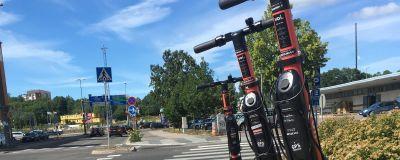 Tre elsparkcyklar står vid sidan av en trottoar.