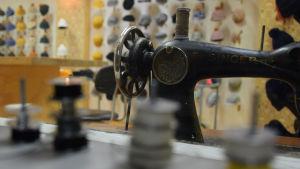 Gammal Singer-symaskin med rader av hattar i bakgrunden och trådrullar i förgrunden.