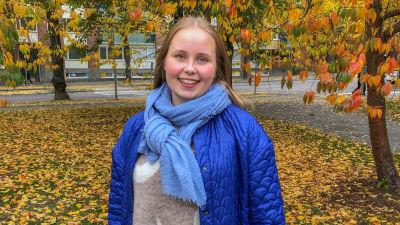 Porträtt på Veronica Helanen utomhus med färggranna höstlöv i bakgrunden.