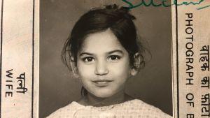 svartvitt passfoto på en liten flicka med mörkt hår och stora ögon