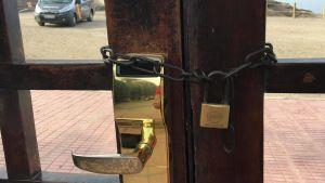 Dörr har försatts med hänglås, på utsidan syns en spansk polisbil.