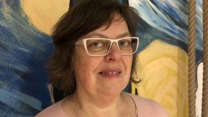 Kvinna i ljus tröja och med glasögon ser mot kameran. Färggran vägg i bakgrunden.
