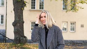 Kvinna som står framför en byggnad och höstlov på marken. Hon har ena handen i sitt blonda hår och den andra i jeansfickan. Hon ler och tittar åt vänster.