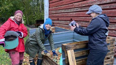 Tre kvinnor står vid en kompost, två tittar in i kameran och den tredje filmar.