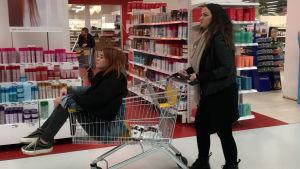 Miia työntää ostoskärryjä, joissa Ansku istuu kyydissä.