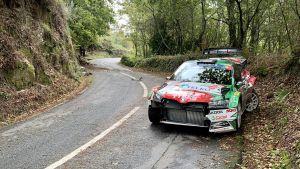 En tilltufsad rallybil står vid vägkanten.
