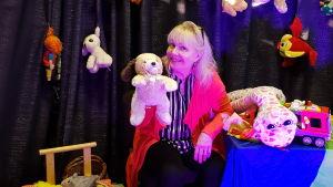 En kvinna sitter omringad av mjukisdjur och leksaker med en handdocka.