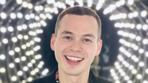 Siilitukkainen nuori mies hymyilee suu auki kameralle, taustalla näkyy pieniä hehkulamppuja. Päällään miehellä on kukallinen kauluspaita, jonka päällä on musta pikkutakki.
