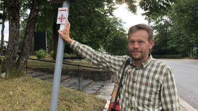 James Simpson, pekar på Sankt Olofs pilgrimsmärken, som markerar vandringsleden.