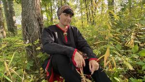 På bilden syns Maura Häkki som sitter och poserar i ett skogslandskap.